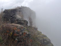 Fog rolling over cliff edge. A fog bank rolling over a craggy cliff Royalty Free Stock Image