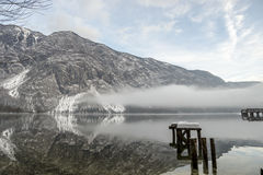 Fog rolling in on water under mountains Stock Image