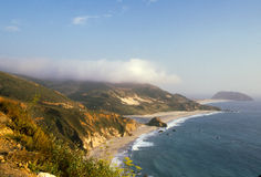 Fog Rolls in on Big Sur Beach. Long stretch of sandy beach with rocky cliffs and wild flowers in the foreground and thick fog rolling in over the hills in the Stock Images