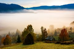 Fog in the rural valley. Gorgeous sunrise in autumn mountains. haystack trees on the grassy hill Stock Photo