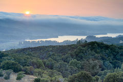 Fog slides over the hills in a thick white blanket. Royalty Free Stock Images