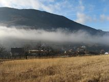 A fog strip above a Slovak village in Strazov hills Royalty Free Stock Photos
