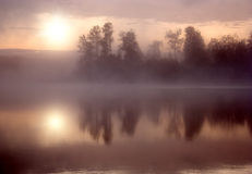 Fog Sun Morning Lake. Morning nature scene (landscape): the sun in fog (mist) reflected on the water surface (lake, river, pond) along with opposite shore and stock photos