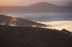 Fog trough the hills on autumn morning Royalty Free Stock Image