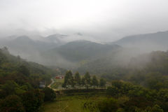 Fog village in the valley of tianzhushan ( tianzhu mountain ). The mountain village in fogand rain, amoy city, china. it is far from the madding crowd Stock Photo