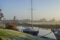 Fog, windmills and boats on a river Stock Images
