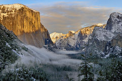 Fog in Yosemite Valley with El Capitan and Half Dome, Yosemite National Park. Snow covered trees in fog in Yosemite Valley with El Capitan and Half Dome in view Royalty Free Stock Photos