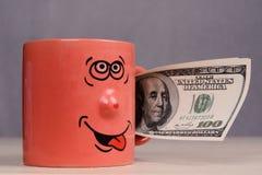 Foggi a coppa con i soldi dei dollari nella mano Fotografia Stock