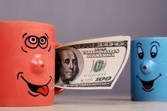 Foggi a coppa con i soldi dei dollari nella mano Fotografia Stock Libera da Diritti