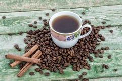 Foggi a coppa il caffè con i fagioli e la cannella sulla tavola rustica verde Struttura di legno Fotografie Stock