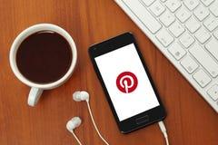 Foggi a coppa il caffè e lo Smart Phone con il logo di Pinterest sul suo schermo Fotografie Stock Libere da Diritti