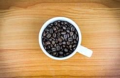Foggi a coppa in pieno dei chicchi di caffè sullo scrittorio di legno Immagini Stock