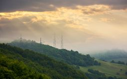 Power line tower on the hill touch the cloud. Foggy autumn countryside in mountains. power line tower on the forested hill touch the cloud. beautiful golden royalty free stock photography