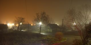 Foggy autumn evening. Street lighting and fog. A halo of light. High point shooting. royalty free stock photography