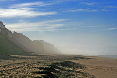 Foggy beach. Scenic view of fog and cliffs on beach with blue sky and cloudscape background, Santa Cruz, California, U.S.A Royalty Free Stock Photography
