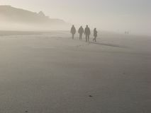 Foggy beach. Hikers in the morning mist at the west beach of Sylt island, Germany Stock Image
