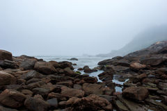 Foggy beach with rocks and mist at nightfall Stock Photo