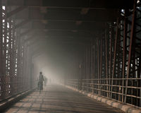 A foggy bridge with a cyclist Stock Photography