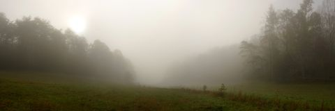 Foggy Cades Cove Panorama. The sun rising over a peaceful Cades Cove, a valley of the Great Smoky Mountains National Park, USA, shrouded in fog this morning stock photos