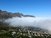 Camps Bay from Lions Head. Aerial landscape shot of the clouds moving over Camps Bay with clouds mountains and blue sky, South Africa royalty free stock photo