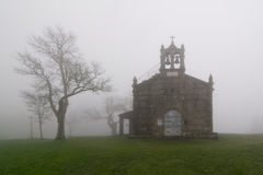Foggy church. And tree without people Stock Photos