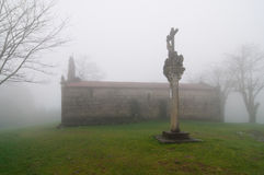 Foggy church and cross. Church and sculpture of a cross in a very foggy day Royalty Free Stock Photography