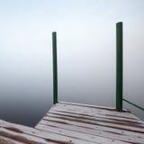 Foggy coastal abstract, frozen wooden pier. Foggy coastal abstract fragment with frozen wooden pier stock photo