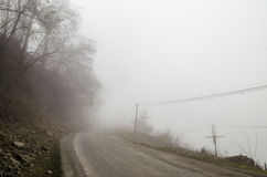 Foggy Country Road. Fog creates a feel of emptiness as it leads to seemingly nowhere. Ilisu, Gakh, Azerbaijan Stock Photo
