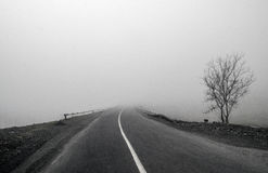 Foggy Country Road. Fog creates a feel of emptiness as it leads to seemingly nowhere. Ilisu, Gakh, Azerbaijan Royalty Free Stock Photography