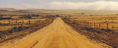 Foggy Countryside Road. Foggy Countryside Gravel Road in Central Colorado, United States of America. Panoramic Photo stock image