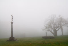 Foggy cross. An sculpture of a cross in a foggy day Stock Images