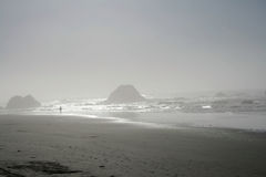 Foggy day at the beach. Foggy day with large rocks in the surf. Person strolling visible in the distance Royalty Free Stock Photography