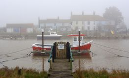Foggy day at the river Blyth Southwold Suffolk with pier and Red Fishing Boat. Foggy day at the river Blyth Southwold, Warbleswick Suffolk with pier and Red stock photos
