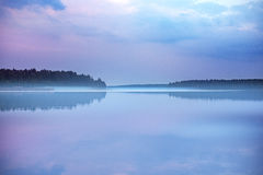 Foggy early morning sunrise on a mirror surfaced lake Stock Images