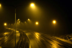 Foggy empty highway. With street lights at night royalty free stock photos