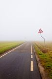 Fog along empty rural road with danger sign Stock Photography