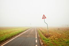 Fog along empty rural road with danger sign Royalty Free Stock Photography
