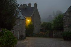 Foggy evening in Locronan,  burning street lamp Royalty Free Stock Photos