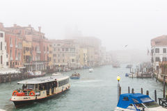Foggy Grand Canal in Venice with Vaporetto and boats. Stock Photos