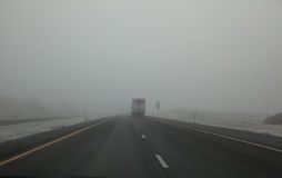 Foggy highway. Tractor Trailer Truck traveling in heavy fog on road in winter; wide angle view royalty free stock image