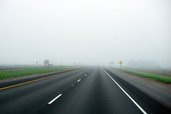 Foggy highway with dividing strip marking of green grass and tru Royalty Free Stock Images