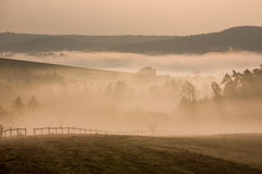 Foggy hills in autumn dawn, Czech. Foggy hills and valleys with fence in autumn dawn Royalty Free Stock Image