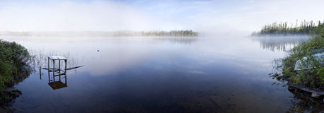 Foggy Lake. Panoramic view of lake with early morning fog Royalty Free Stock Photo