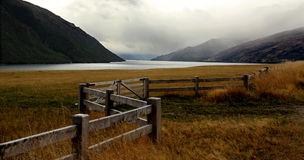 Foggy lake and mountains and farm with withered grass and zigzag fence Stock Images