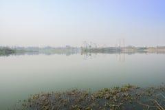 Foggy lake near modern city at sunny winter noon Stock Photos