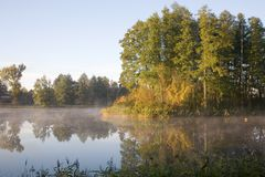 Foggy lake at sunrise. Smoky pond in the morning stock photo
