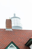 Foggy Lighthouse Beyond Red Tile Roof Stock Photography