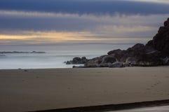 Foggy mist over the surf on a rocky coast. And sundown Royalty Free Stock Photos