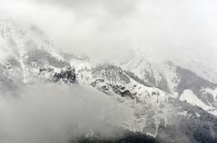A foggy misteric panoramic view of the Alps mountains partially covered with the snow on a cloudy October royalty free stock images