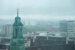 Foggy Misty London Skyline. High rise buildings of London dominated in the foreground by an historic green copper coated tower topped by a weather vane. Muted Stock Photos